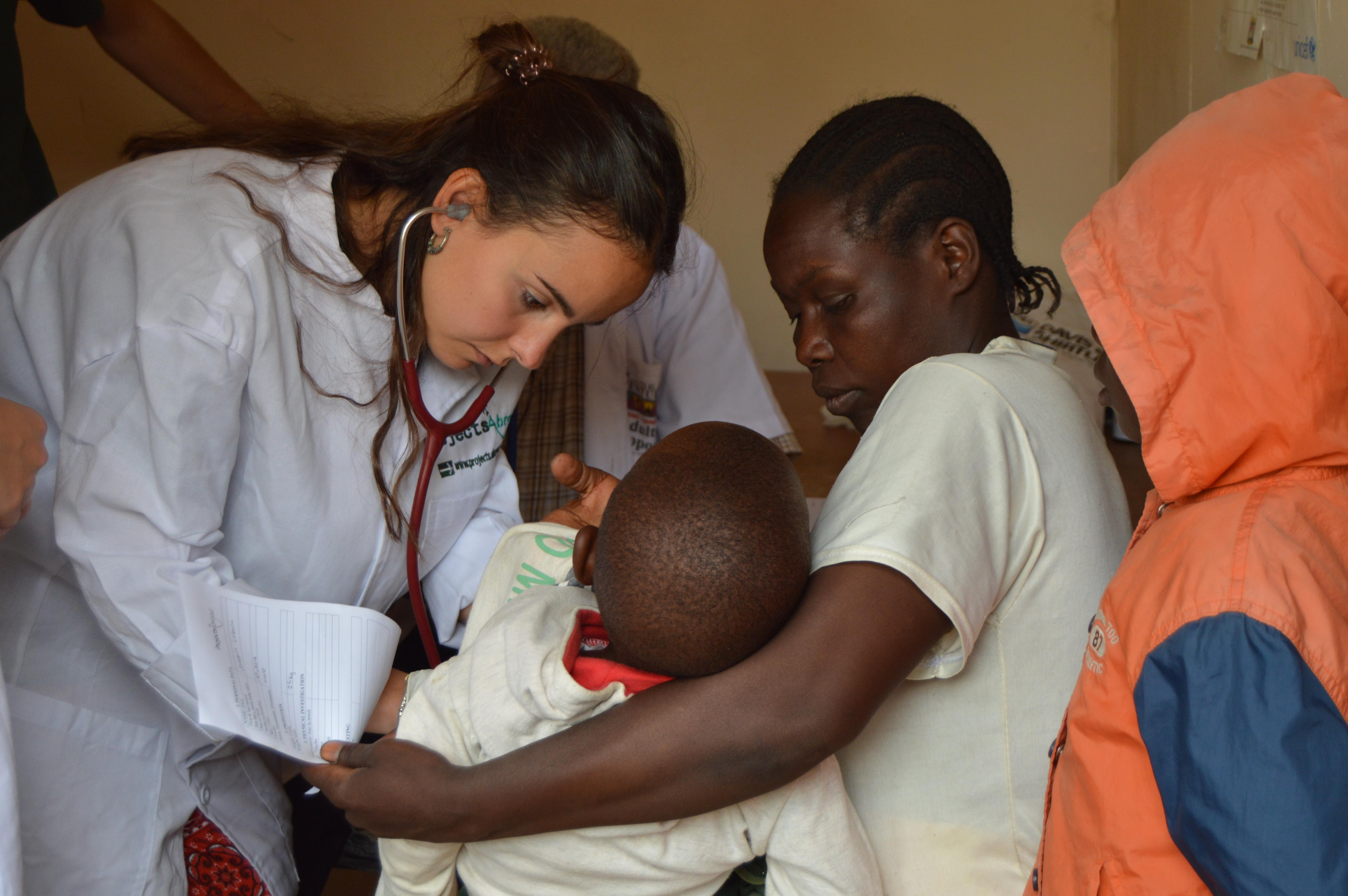 A French Projects Abroad intern is seen examining a child during a medical outreach whilst she completes her nursing internship in Tanzania.
